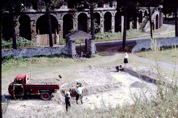 A red ute and five people working in a shallow ditch outside an amphitheatre